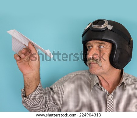 Senior funny man as a pilot with hat and glasses using paper plane - stock photo