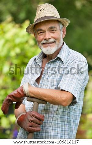 Senior gardener with a spade in the garden - stock photo