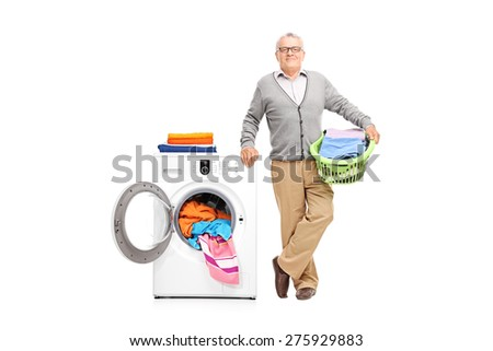Senior gentleman holding a laundry basket full of clothes and posing next to a white washing machine isolated on white background - stock photo