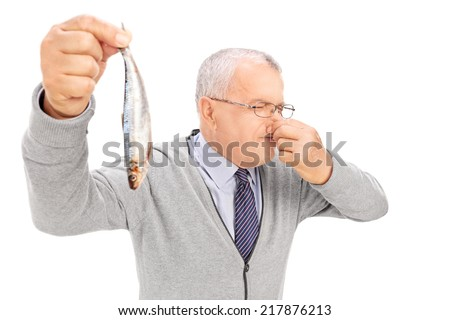 Senior gentleman holding a rotten fish isolated on white background - stock photo