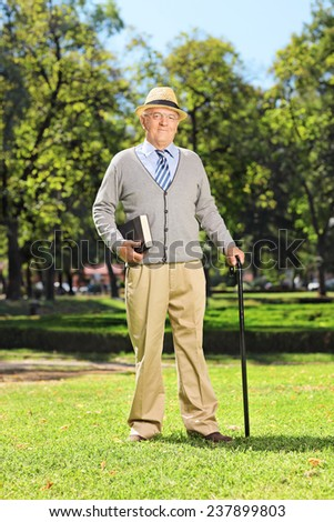 Senior gentleman posing in park on a beautiful summer day  - stock photo