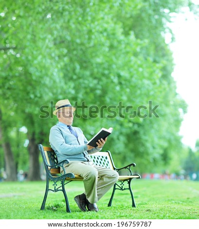 Senior gentleman reading a book in park seated on wooden bench shot with tilt and shift lens  - stock photo