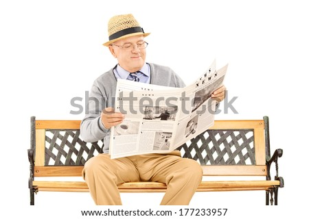 Senior gentleman reading newspaper on a bench isolated on white background - stock photo