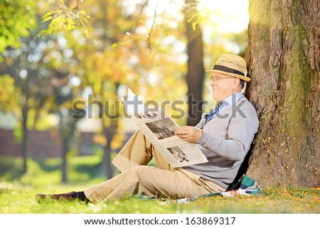 Senior gentleman seated on a grass reading a newspaper in a park at autumn - stock photo