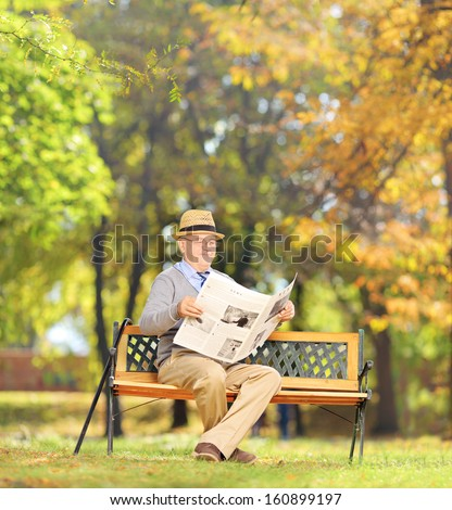 Senior gentleman seated on a wooden bench reading a newspaper in a park, shot with a tilt and shift lens - stock photo