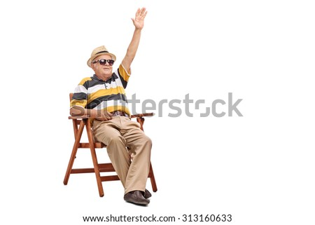 Senior gentleman sitting in a wooden chair and waving to someone with his hand isolated on white background - stock photo
