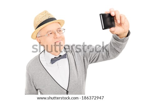 Senior gentleman taking a selfie with cell phone isolated on white background - stock photo