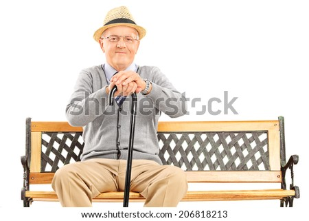 Senior gentleman with a cane sitting on bench isolated on white background - stock photo