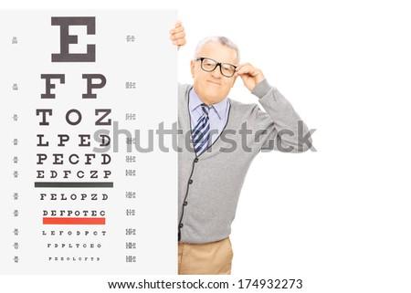 Senior gentleman with glasses standing behind eyesight test isolated on white background - stock photo