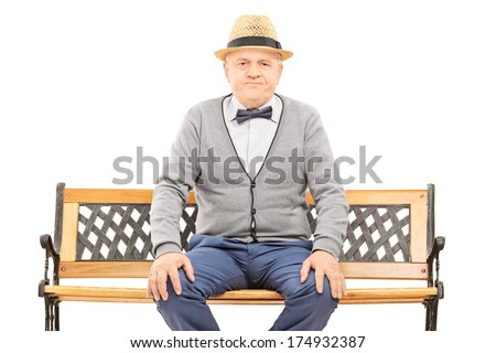 Senior gentleman with hat seated on bench looking at camera isolated on white background - stock photo