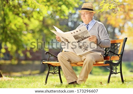 Senior gentleman with hat sitting on a wooden bench and reading a newspaper in a park - stock photo