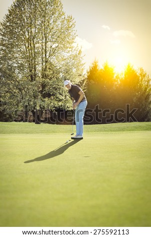Senior golf player putting on green at sunset, with blank copyspace. - stock photo