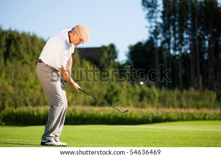 Senior golfer doing a golf stroke, he is playing on a wonderful summer afternoon - stock photo
