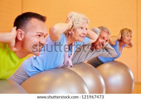 Senior group in back training class exercising in fitness center - stock photo