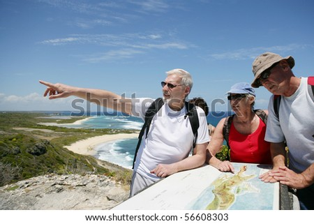 Senior group of hikers watching a plan - stock photo