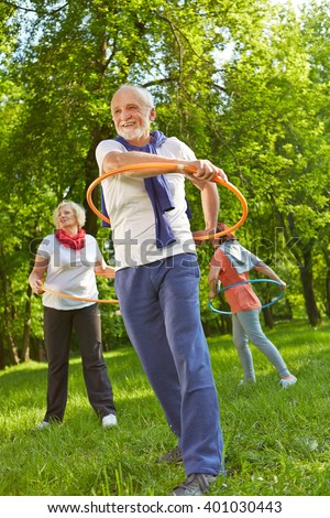 Senior group with hoops in a fitness class exercising in nature in a garden - stock photo