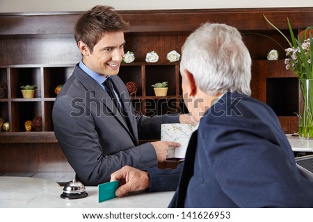 Senior guest in hotel asking receptionist for the way - stock photo