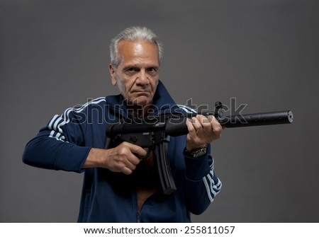 senior gunman with automatic rifle in front of grey background - stock photo