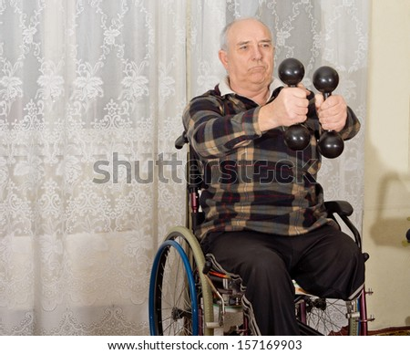 Senior handicapped man exercising with a pair of dumbbells to strengthen his arms while sitting in a wheelchair - stock photo