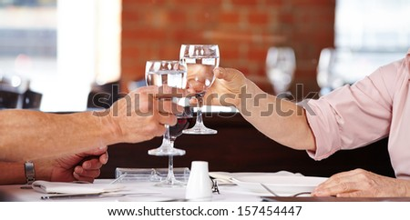 senior hands clinking glasses with water in a restaurant - stock photo