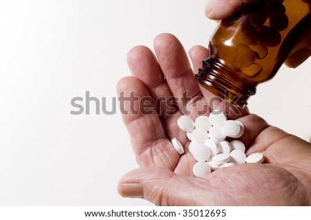 Senior hands pouring out tablets - stock photo