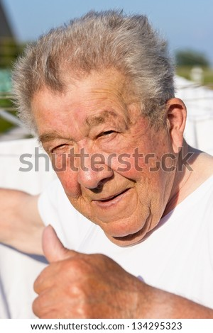 Senior hangs up the laundry in the garden to dry - stock photo