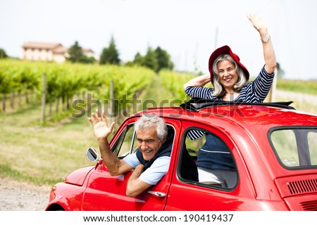 Senior happy couple driving vintage car - stock photo