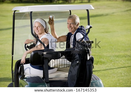 Senior happy couple on the golf cart - stock photo