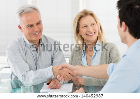 Senior Happy Couple Shaking Hand With Financial Advisor - stock photo