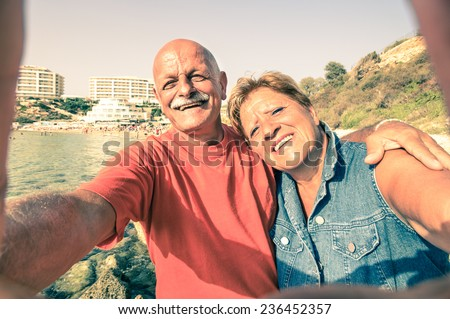 Senior happy couple taking a selfie at Blue Grotto resort in Malta south coast - Adventure travel to mediterranean islands - Concept of active elderly and fun around the world with new technologies - stock photo
