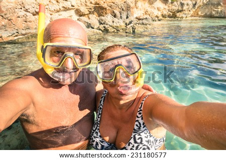 Senior happy couple taking a selfie at Blue Lagoon in Gozo and Comino - Travel to mediterranean island of Malta - Concept of active elderly and fun around the world experimenting new technologies  - stock photo