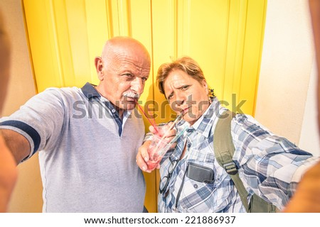 Senior happy couple taking a selfie while eating a granita crushed ice cream - Concept of youthful active elderly and interaction with new technologies and trends - stock photo