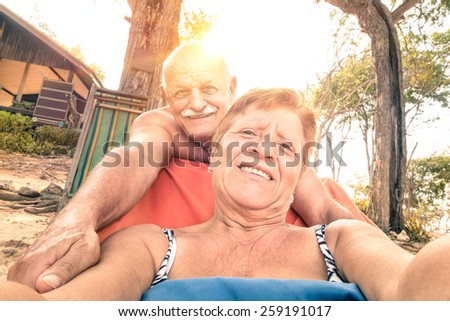 Senior happy couple taking selfie in Thailand trip - Adventure concept of active elderly and fun around the world  - Warm filtered look with genuine tilted horizon and soft focus due to backlighting - stock photo
