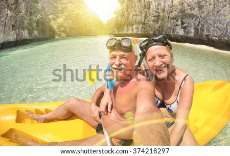 Senior happy couple taking selfie on kayak at Big Lagoon in El Nido Palawan - Travel to Philippines wonders - Active elderly concept around the world - Lens flare and sun halo are part of composition - stock photo