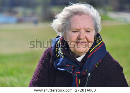 Senior happy woman dreaming in garden. MANY OTHER PHOTOS FROM THIS SERIES IN MY PORTFOLIO.  - stock photo