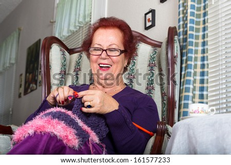 Senior happy woman laughing while knitting, she sits on a fancy old classic style chair - stock photo