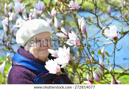 Senior happy woman smiling in garden full of magnolia flowers. MANY OTHER PHOTOS FROM THIS SERIES IN MY PORTFOLIO.  - stock photo