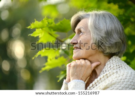 Senior happy woman smiling on background of green summer leaves - stock photo