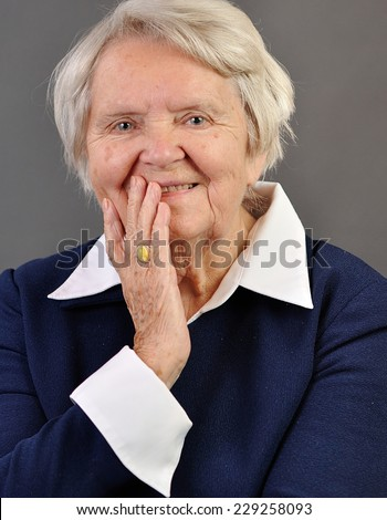 Senior happy woman with grey hairs against grey background.  - stock photo