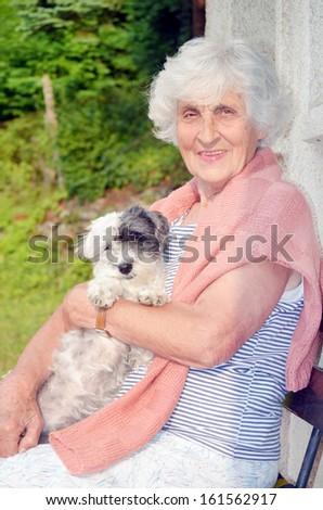 Senior happy woman with her white  dog - stock photo