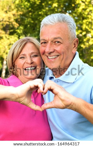 Senior healthy couple showing heart and smiling outdoor. Valentine`s day concept - stock photo
