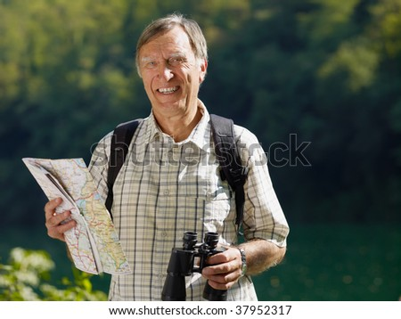 senior hiker holding map and binoculars and looking at camera. Copy space - stock photo
