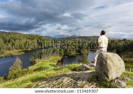 Senior hiker looks over Tarn Hows in English Lake District - stock photo