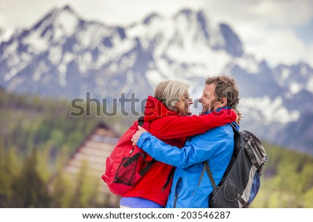 Senior hikers couple hugging during the walk in beautiful mountains, hills and hotel in background - stock photo