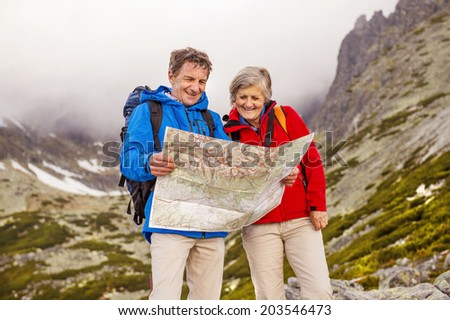 Senior hikers couple looking at the hike map during the hike in beautiful mountains - stock photo