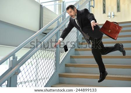 Senior Hispanic businessman falling on stairs - stock photo