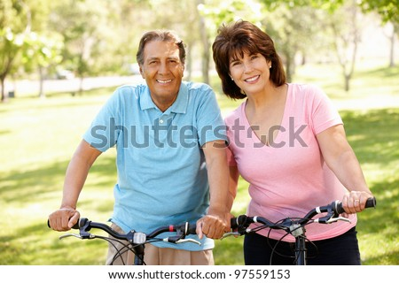 Senior Hispanic couple on bikes - stock photo