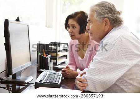 Senior Hispanic couple working on computer at home - stock photo