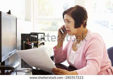 Senior Hispanic woman working on computer at home - stock photo