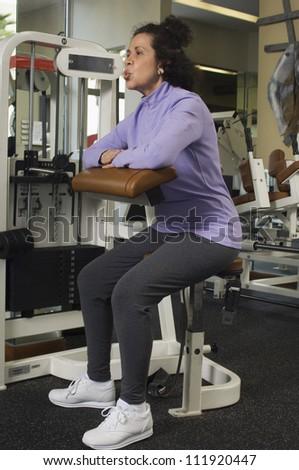Senior hispanic woman working out in gym - stock photo